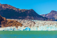 Massive glacier and ice-floes. Massive glacier descends into the emerald water. In the water ice-floes, broken away from a glacier. The picturesque multi-colored royalty free stock image
