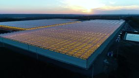 Aerial shot of massive greenhouses, beautiful sunset on the background. Massive glasshouses from high angle, with colorful sunset on the background, aerial shot stock video