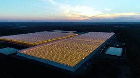 Massive greenhouses with light coming out of them, with sunset on the background. Two big glasshouses, and colorful beautiful sunset on the background, aerial stock footage