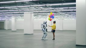 Massive hall with a robot getting balloons from a lady stock footage