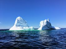 A massive iceberg floating off the coast of Twilingate, Newfoundland and Labrador, Canada. The iceberg floats in the vast open stock image