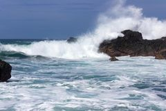 Massive implacable waves of the Pacific Ocean crash upon the unbreaking volcanic rock of Costa Rica`s Playa San Janillo. Stock Photography