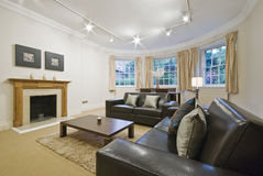 Massive living room with bay window. And luxury leather sofas royalty free stock photography