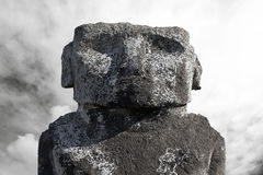 Massive moai head against cloudy sky Stock Photos