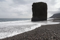 Massive monolith rock on an Icelandic beach. Horizontal view of an Icelandic beach with a huge rock formation in the middle Stock Photo