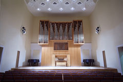 Massive pipe organ in empty concert hall. Massive wooden pipe organ in empty concert hall; rows of seats Royalty Free Stock Image