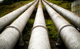 Massive Pipes. Massive hydro electric pipelines converge up a hill Royalty Free Stock Image