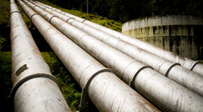 Massive Pipes. Massive hydro electric pipelines converge up a hill Stock Photography