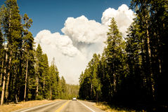 Towering Wildfire Clouds. Massive plumes of smoke rise above the road and forest in Yellowstone Park near a dangerous wildfire Royalty Free Stock Photo