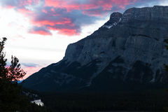 Massive Rocky Mountain and Pink Sunrise Clouds. Mt Rundle with beautiful pink clouds from sunrise Stock Photo