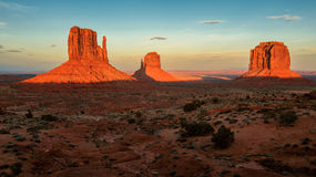 Massive sandstone pillars soar above iconic Monument Valley at sunset. Arizona, USA Stock Image