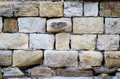Massive a stone masonry with grey, light brown rectangular rocks. Erased adhesive mixture. Great weighing in its place hard, thick wall royalty free stock image