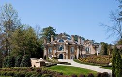 Massive Stucco Mansion on Landscaped Hill Stock Photo