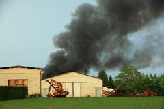 Massive toxic black cloud in the sky rises from a fire Stock Photo