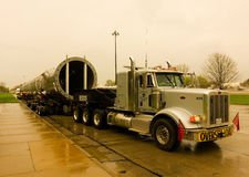 A massive trailer carrying a l large, heavy part at a rest area in america Stock Photos