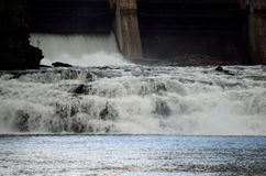 Massive waterfall as concrete water barrier opens. On hydro electrical power plant in northern norway stock photos