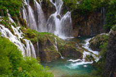 Massive waterfall among lush foliage. Scene in Plitvice Lakes National Park Royalty Free Stock Images