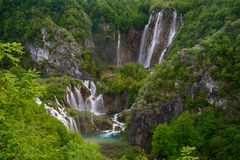 Massive waterfall among lush foliage. Scene in Plitvice Lakes National Park Stock Photos