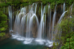 Massive waterfall in Plitvice Lakes. Massive waterfall downs to green lake. Waterfall is surrounded with green foliage Stock Images
