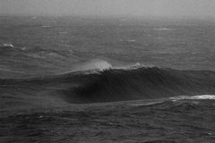 Massive Wave Breaking on Shallow Reef Black and White. A massive wall of water rears upward in a storm before crashing onto a very shallow rock shelf Stock Image