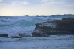 Massive ocean waves surge over rock outcrop. Massive ocean waves coming in and surging over rock outcrop at Swami`s Beach in Encinitas, California royalty free stock photo