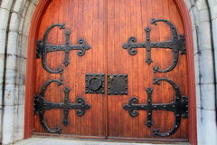 Massive wood doors with heavy metal embellishments. Imposing wood doors with heavy metal embellishments, entrance in old,stone building Stock Photography