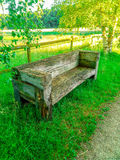 Massive wooden bench in green Stock Photos