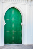 Massive wooden green door. Massive Arabic style green door in a white wall Royalty Free Stock Photos