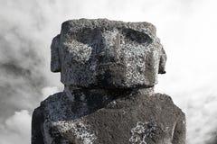 Massivt moaihuvud mot den molniga skyen Arkivfoton