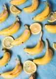 Massor av bananer och citroner på en blå bakgrund Royaltyfri Foto