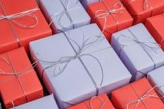 Massor av blandninggåvor som slås in i rött och lila papper arkivfoto