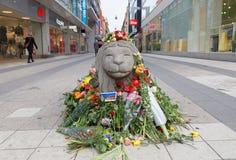 Massor av blommor på konkret lejon i centrala Stockholm från peopl Arkivbilder