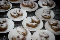 Massor av donuts, donuts på plattor, efterrätt, rullar i dammet Arkivfoto