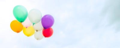 Massor av färgrika ballonger på den blåa himlen, begreppet av förälskelse i sommar och valentin som gifta sig bröllopsresa - pano Royaltyfri Bild