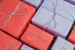 Massor av festliga gåvor som slås in i rött och lila papper royaltyfria foton