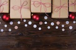 Massor av gåvaaskar på träbakgrund med konfettier Stilfulla gåvor i hantverkpapper dekorerade med det randiga röda och vita bande Fotografering för Bildbyråer