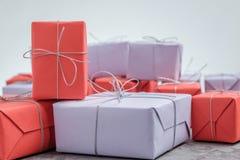 Massor av gåvor som slås in i rött och lila papper arkivbild