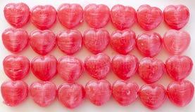 Massor av hjärta-formad röd godis som är ordnad som bakgrund arkivfoton