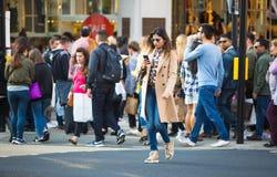 Massor av människor, turister, Londonersshoppare som korsar den härskande gatan Befolkat stadsbegrepp london uk Royaltyfri Bild