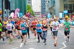 Massor av m?nniskor som k?r i den London maraton Folk som hurrar idrottsm?nnen i Canary Wharf omr?de royaltyfria foton