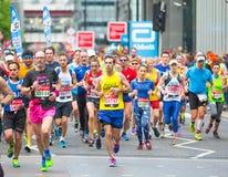 Massor av m?nniskor som k?r i den London maraton Folk som hurrar idrottsm?nnen i Canary Wharf omr?de royaltyfria bilder