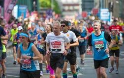 Massor av m?nniskor som k?r i den London maraton Folk som hurrar idrottsm?nnen i Canary Wharf omr?de arkivfoto