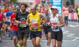 Massor av m?nniskor som k?r i den London maraton Folk som hurrar idrottsm?nnen i Canary Wharf omr?de royaltyfri foto