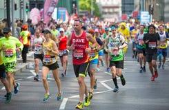 Massor av m?nniskor som k?r i den London maraton Folk som hurrar idrottsm?nnen i Canary Wharf omr?de royaltyfri fotografi