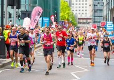 Massor av m?nniskor som k?r i den London maraton Folk som hurrar idrottsm?nnen i Canary Wharf omr?de arkivbilder