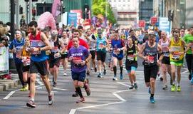 Massor av m?nniskor som k?r i den London maraton Folk som hurrar idrottsm?nnen i Canary Wharf omr?de arkivbild