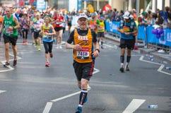 Massor av m?nniskor som k?r i den London maraton Folk som hurrar idrottsm?nnen i Canary Wharf omr?de fotografering för bildbyråer