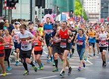 Massor av m?nniskor som k?r i den London maraton Folk som hurrar idrottsm?nnen i Canary Wharf omr?de arkivfoton