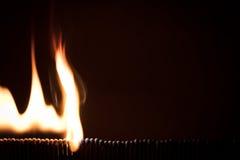 Massor av matchsticks som bränner med en snöbollseffekt, svart backgrou Arkivfoton