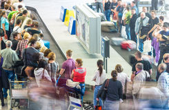 Massor av människor som får bagage på flygplatsen. Arkivbilder